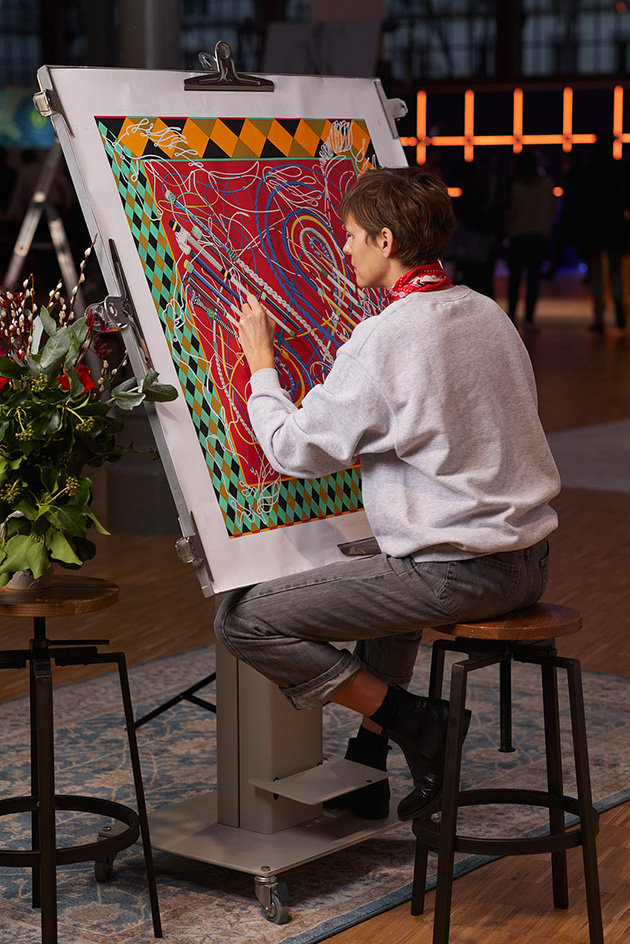 An artist creates a Hermes Carre scarf at its Carre Club exhibition in Paris