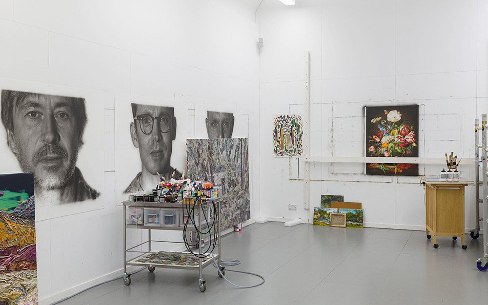 A view of Jason Brooks' Gloucestershire studio with hyperrealist portraits and painting utensils