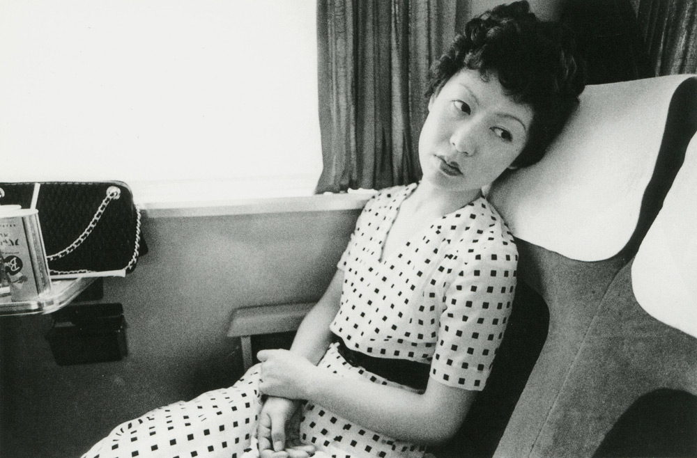 Black and white portrait of a Japanese woman in a white dress leaning back into a seat on a train