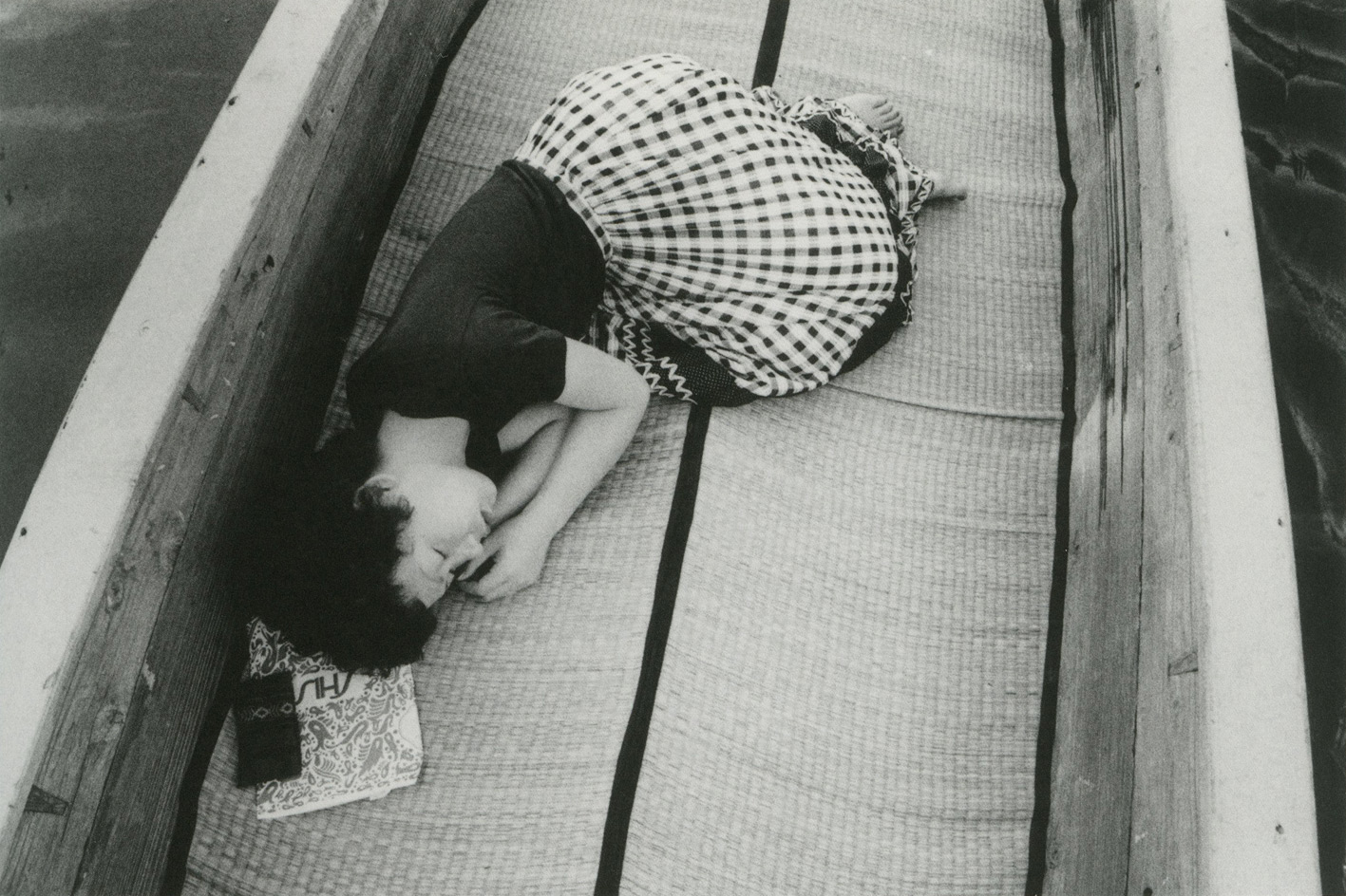 Black and white photograph of a Japanese woman sleeping in a fetal position on a boat