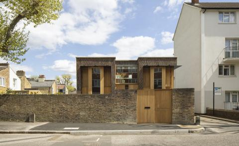 Southwark brick house by Satish Jassal as it sits behind a brick wall on a sleepy residential street in South London