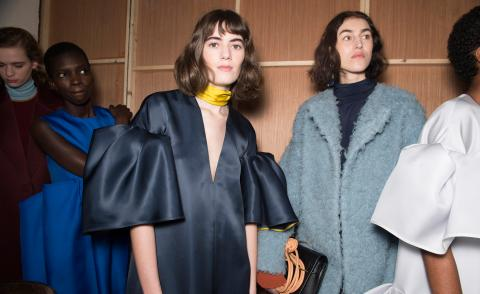 Model wears a navy silk top with exaggerated balloon sleeves, whilst another wears a sky-blue teddy coat