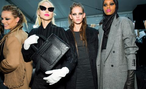 Model holds up a black leather bag dresses in a pinstripe dress, another wears a fringed jacket