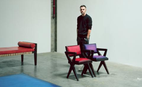 Kris van Assche stands next to Berluti furniture