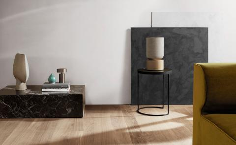 A beige speaker with a wooden base sits on a small coffee table in a minimal lounge