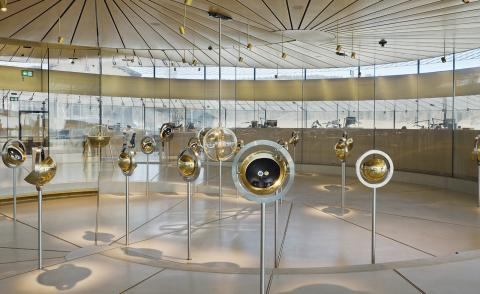 Globe-shaped watch display features gold metal watch holders