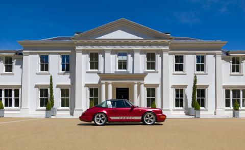 A red porsche car is parked outside a large white house