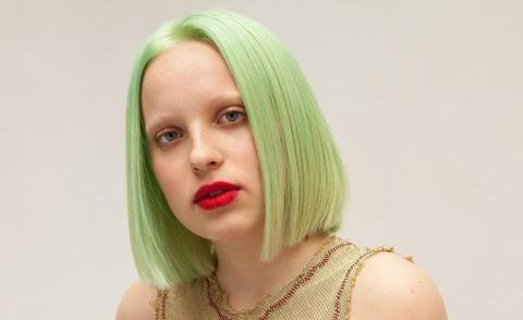 light green straight bobbed hair by Bleach London with red lips and bleached brows