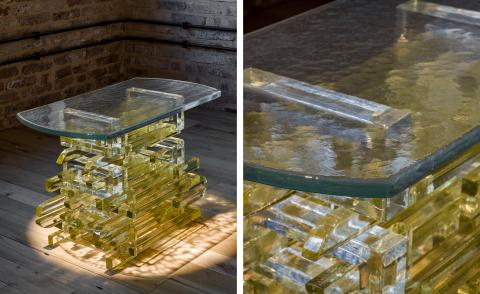 Translucent yellow glass table shown in two different points of view, which was created by Bethan Laura Wood for Wonderglass, placed on a wooden floor in front of a brick wall
