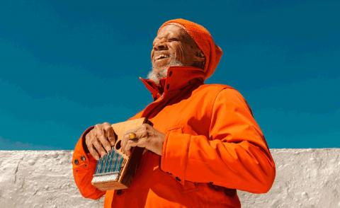 new age musician laraaji dressed in orange and laughing