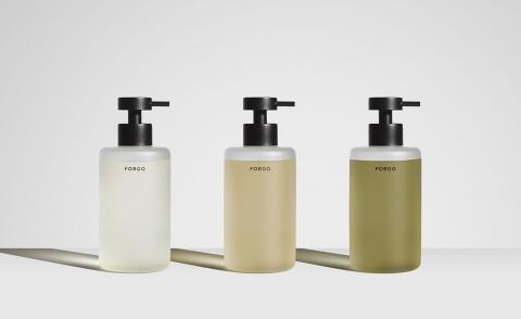 Three Forgo hand wash bottles in refillable containers against grey background