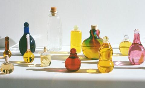 multiple multi-colour handblown glass bottles of skincare products by Kindred Black