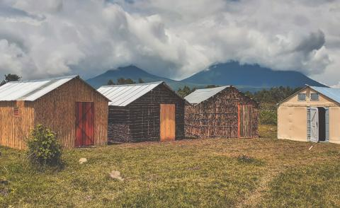 Four shelters built from wood in Rwanda in front of mountains