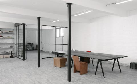 The minimalist interior of Studio Khachatryan's new Brussels space featuring stone tiled floor and all-white walls. The building is a studio as well as exhibition space for the designer's works