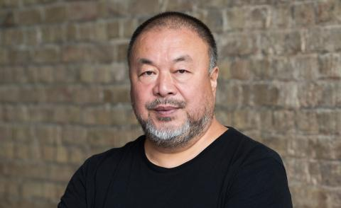 Portrait ofChinese artist Ai Weiwei in his studio with brick background