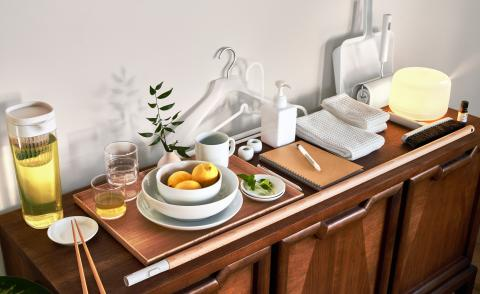 A wooden sideboard with a series of objects by Muji part of a holiday home essentials kit. Including plates and bowls, a jug, a light and scent diffuser, hangers, pen and notebook, towels, and broom and dustpan