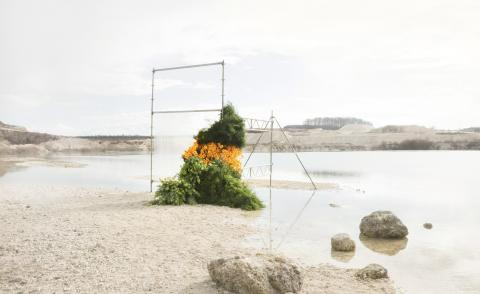 An installation by Tableau at Faxe Kalkbrud, in Denmark, comprising asparagus fern, gerberas and fritillarias, framed by scaffolding and plastic.