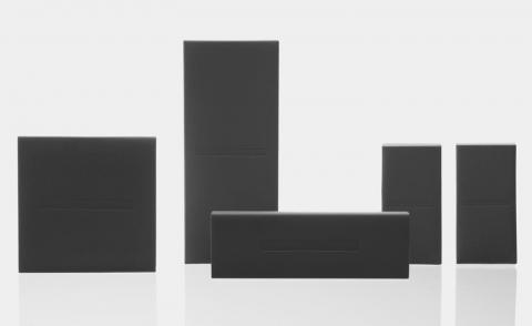 Less skincare packaging of plain black boxes against grey background