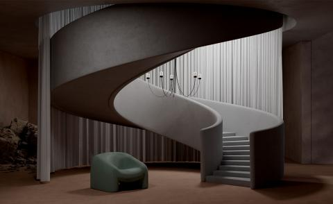 A render showing Paul Cocksedge's Gravity Chandelier for Moooi, a design featuring black curved arms hanging from the ceiling over a spiral staircase. In the background is a large scale gray curtain and a green armchair is on the floor below