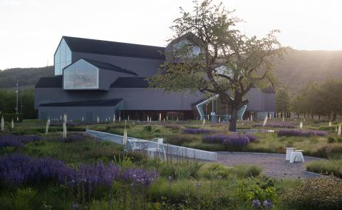 Vitra Haus, a multi-storey building part of the Vitra Campus in Weil am Rhein, Germany, photographed at sunset among greenery and purple flowers, part of Piet Oudolf's garden design
