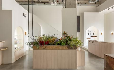 Cadine shop interior with concrete floor and white walls, furniture in granite and ash wood. A large wood and granite desk is visible in the middle of the room, with an installation of colourful wild flowers taking over its whole surface