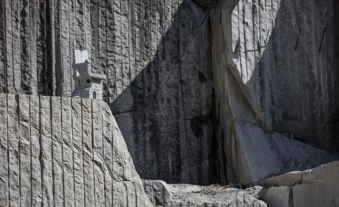 A stone chair by Max Lamb camouflaged on the rocks of a stone quarry in Northern Italy