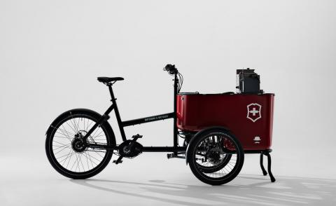 A cargo e-bike with black frame and red bin at the front with the Victorinox logo, consisting in a white cross referencing the Swiss flag