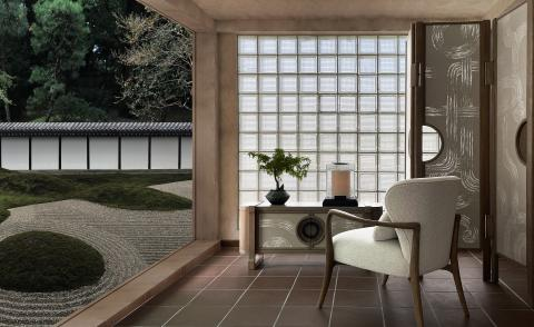 A living room space with furniture by Andre Fu, facing a traditional japanese zen garden with circular raked motifs