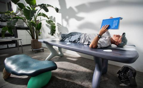 A portrait of Daniel Arsham lying down on a table, reading a blue book