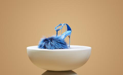 Blue sandal on white curved podium, shoe by Kendall Miles