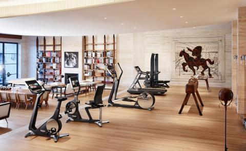 Various pieces of gym equipment in room with white walls and pale wooden floor