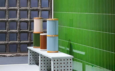 Stacked colourful vases on bench with green tiles in the background