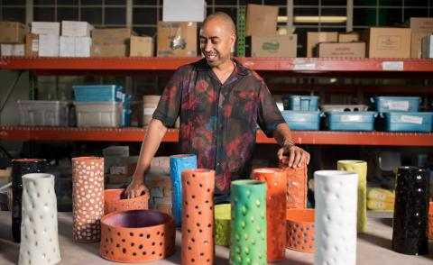 A portrait of designer Stephen Burks in the ceramics workshop at Berea College, surrounded by colourful ceramic vases