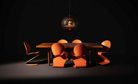 A dark room featuring furniture by Verner Panton, including orange S-shaped chairs and a VP Globe pendant lamp
