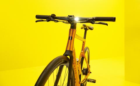 MCM E-bike with copper frame against yellow background