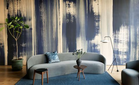 Wallpaper with hand-painted blue stripes with furniture display including grey sofa and freestanding floor lamp on a blue rug
