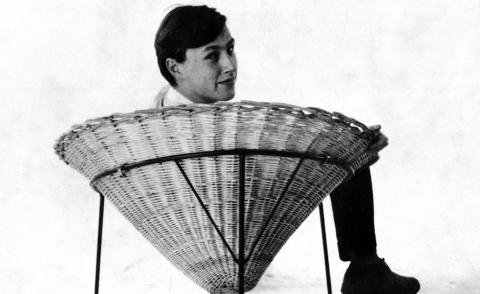 black and white photograph of terence conran on a wicker chair, from 1950s