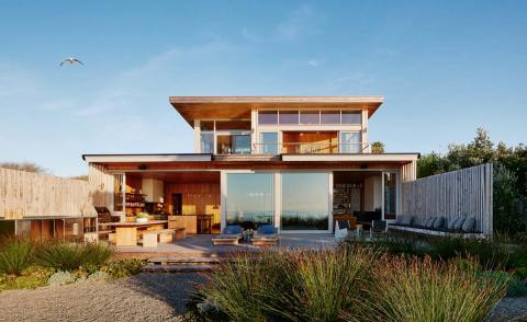 hero image of the Surf House among sand dunes and blue skies