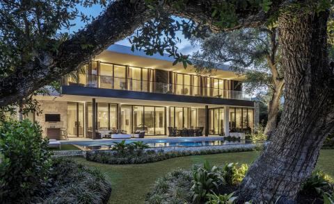 hero exterior with nighttime lighting at the Tarpon Bend Residence by Strang Design