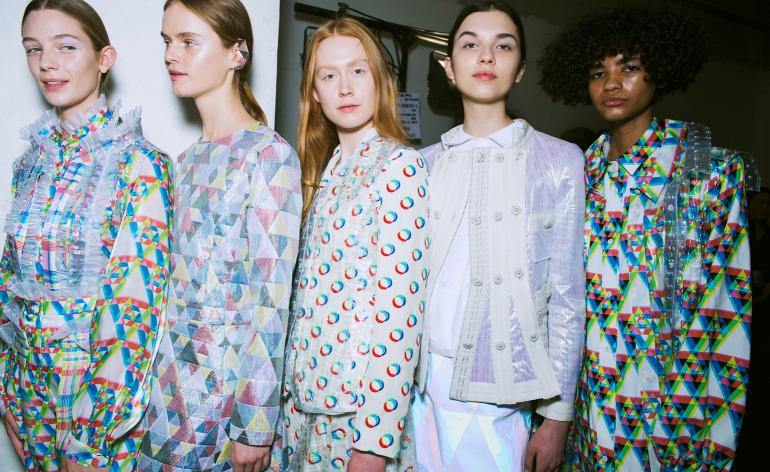 Models wear a range of textured PVC shirts, coats and outerwear. Most include a rainbow, multicoloured details
