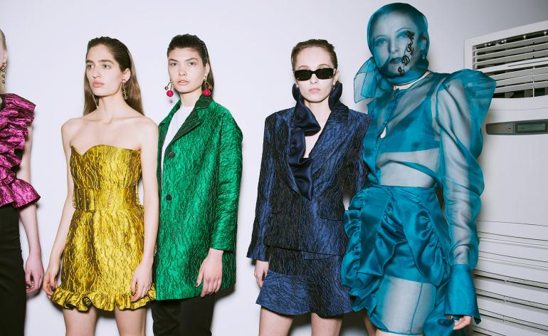 Models wear yellow, green, navy and bright blue dresses and tailored suits. One model wears a blue mesh face mask