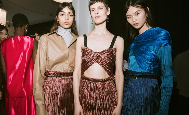 Models are wrapped in metallic-coloured pleats with high-waisted skirts that are fastened with belts