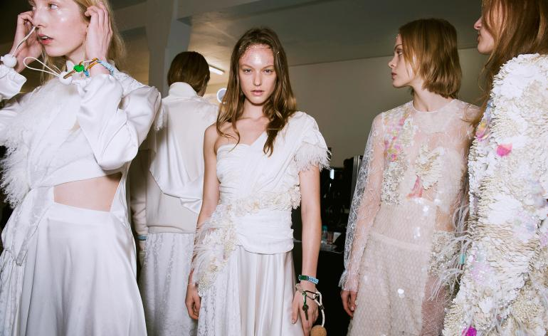 Models wear fill white and pink dresses with embellishments