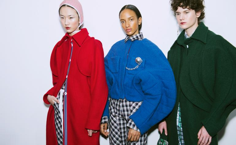 Models wear block colour sweaters with tailored trousers