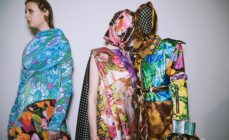 Models wear a range of floral print tops and dresses, some covering heads and faces as a mask