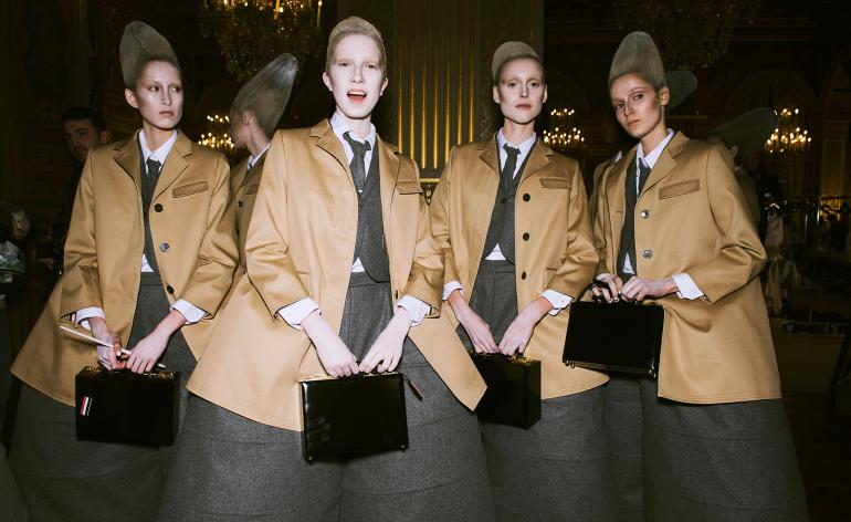 Models are all seen in beige jackets with thick, dark grey skirts with glittery grey wigs