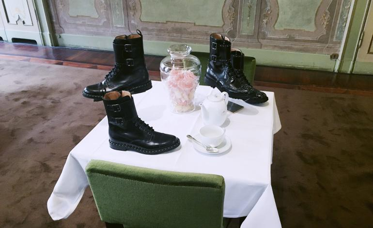 Chelsea boots lie amongst glass bowls and china in an English tearoom set