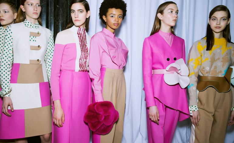 Models wear leather belts, shirts with pleated details, graphic petals and tropical floral prints