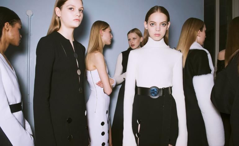 Model wears a white turtle-neck top with a black skirt and plexiglass belt, others wear monochrome overcoats
