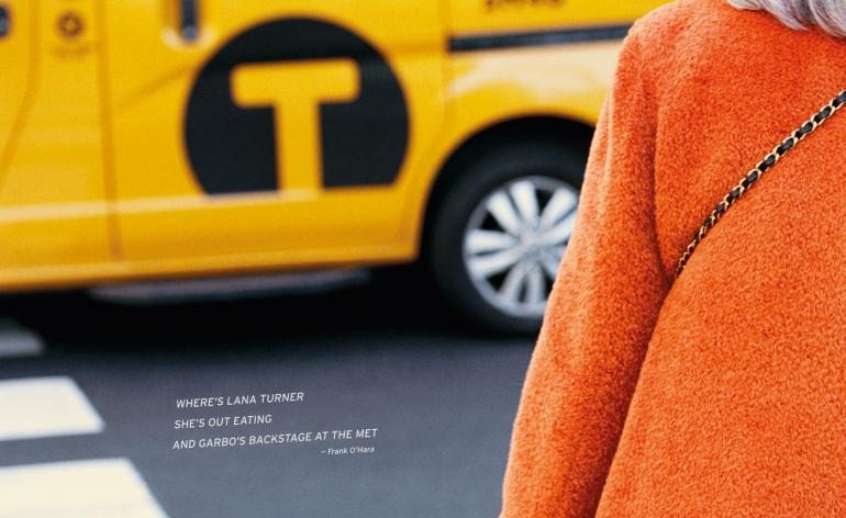 A woman in a bright orange coat passing a New York cab